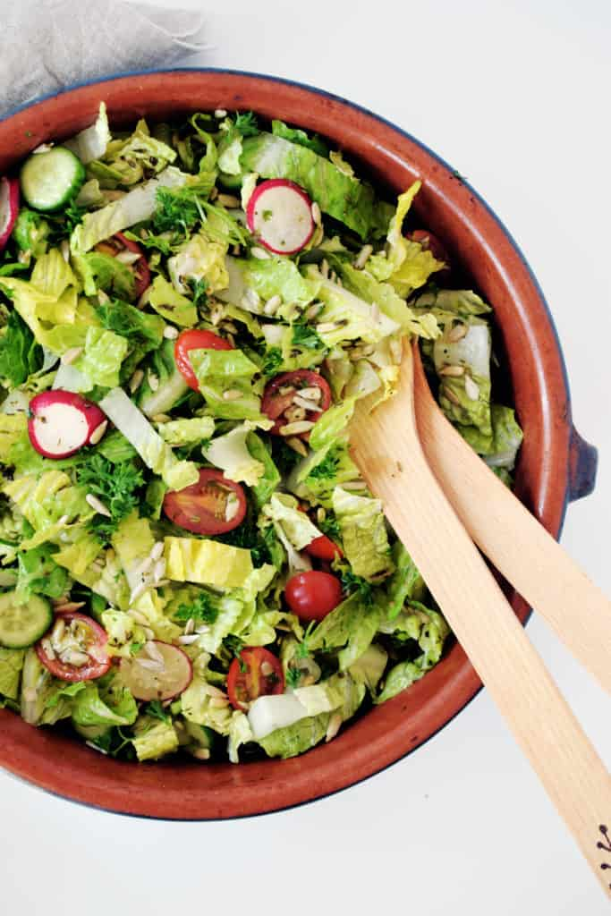 garden salad with herb dressing in brown bowl with wooden salad spoons
