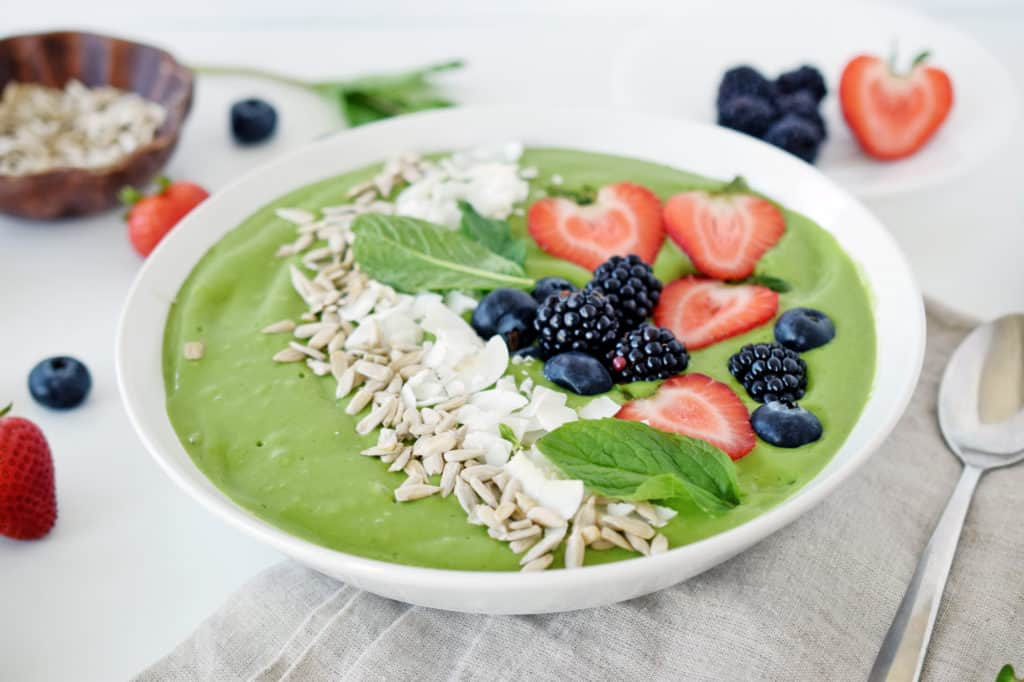 close up of tropical green smoothie in white bowl with silver spoon and berries and background.