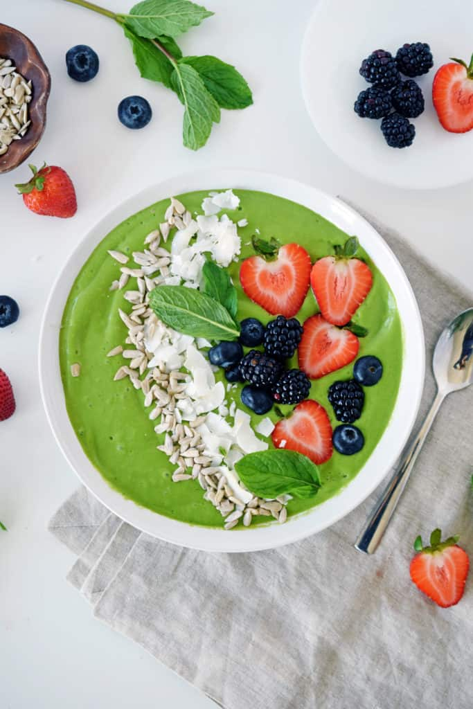 tropical green smoothie bowl with blueberries, strawberries, shredded coconut and sunflower seeds on top. Silver spoon on side with fresh berries sprinkled around.