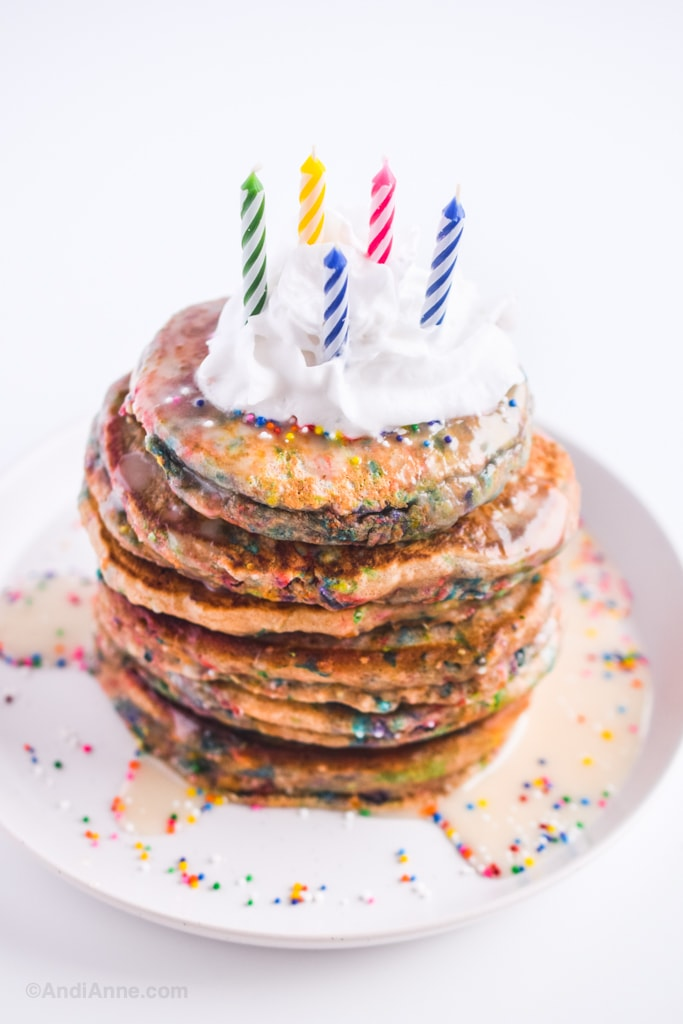 birthday sprinkle pancakes with whipped cream and candles on a white plate