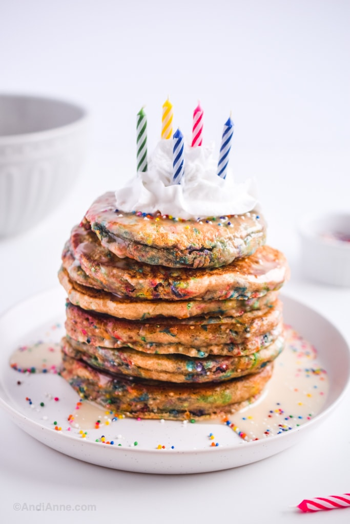 birthday sprinkle pancakes with whipped cream on top and colored candles
