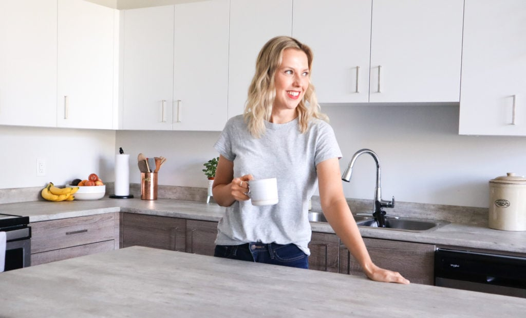 Picture of Andi in her kitchen with coffee cup