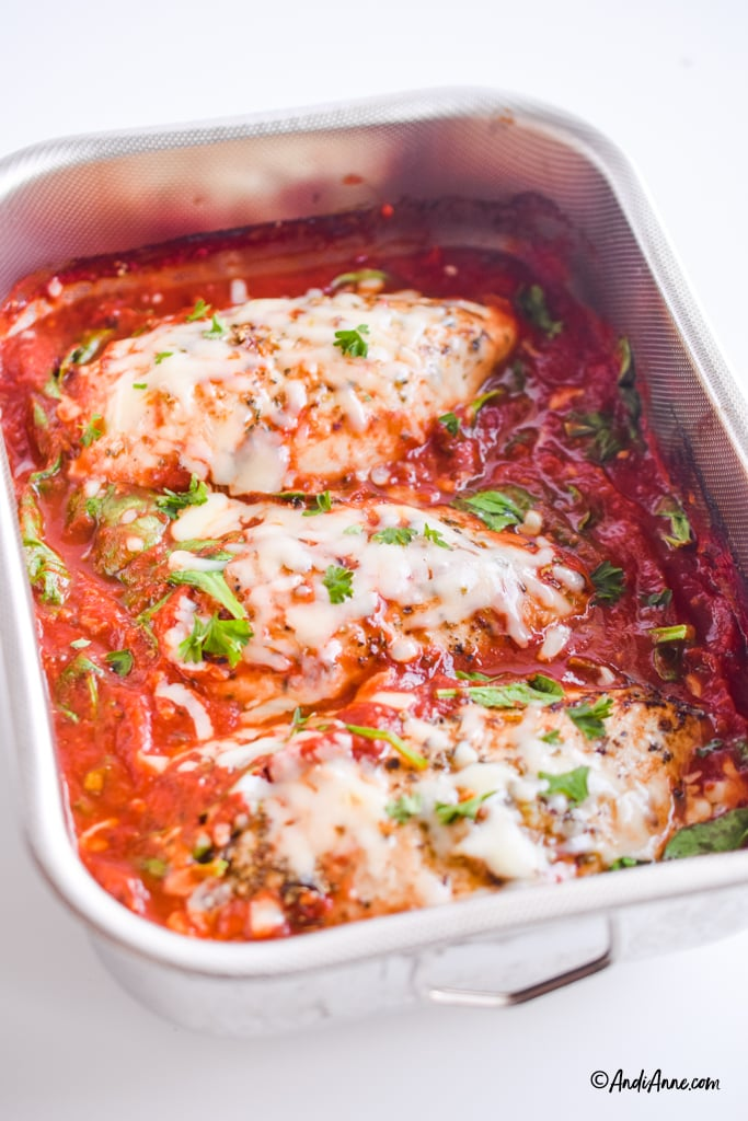 mozzarella chicken in tomato sauce recipe in stainless steel casserole dish. Parsley sprinkled on top of recipe.