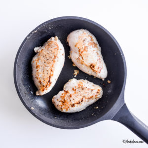 3 chicken breasts in a black frying pan cooking
