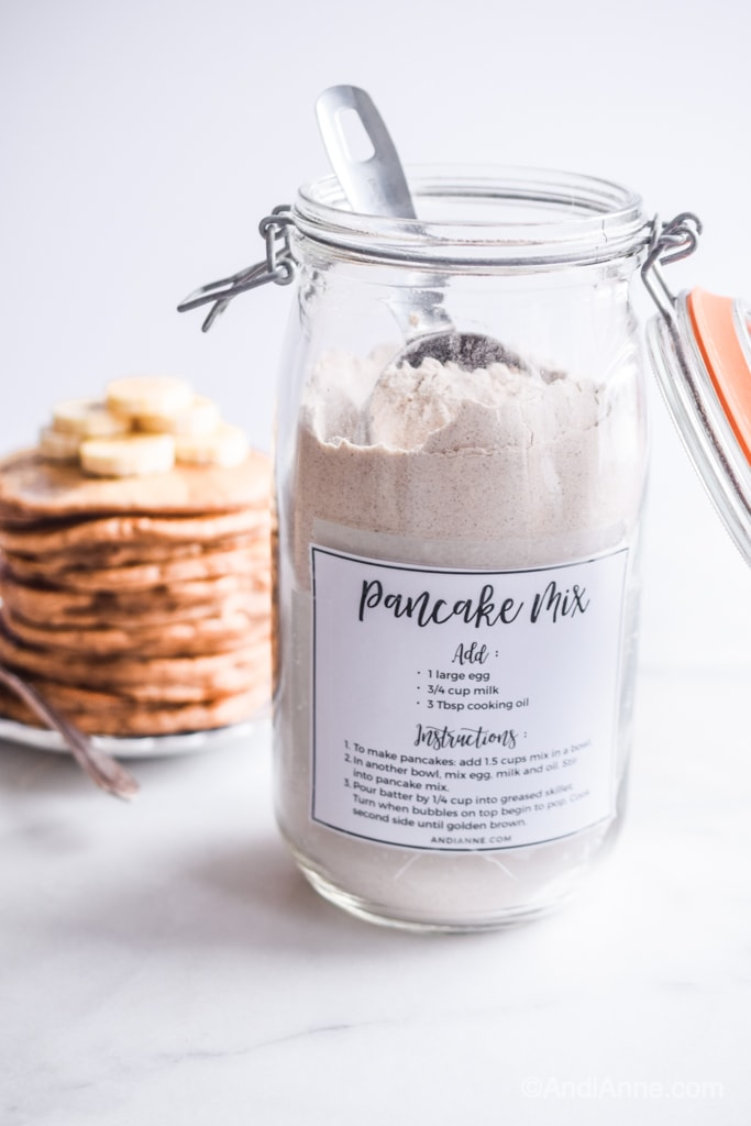 homemade pancake mix in a jar with pancakes stacked in background