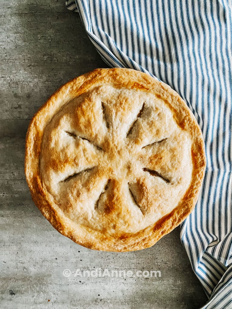 homemade pie crust cooked with striped blue and white towel