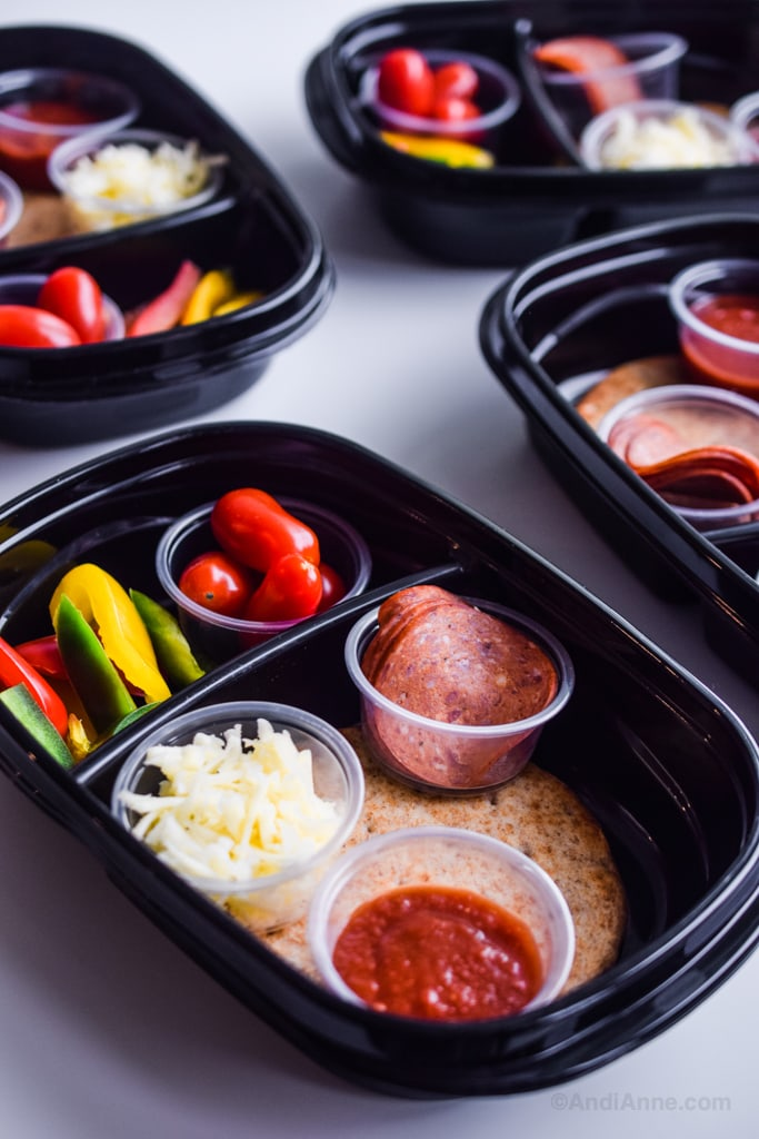 Close up detail of black meal prep containers with smaller clear cups inside holding ingredients separately
