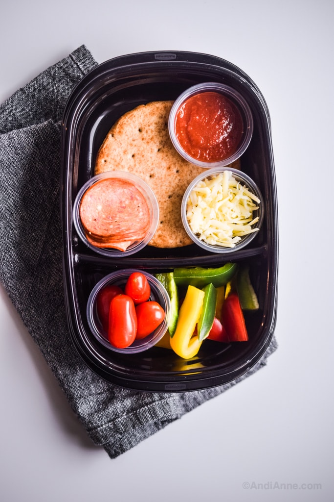 homemade pizza lunchables in meal prep container on a counter with a cloth