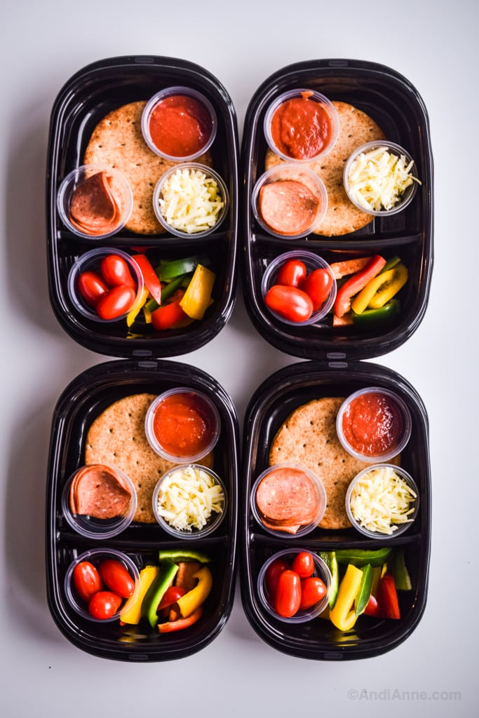 Homemade pizza lunchables stacked side by side in black containers