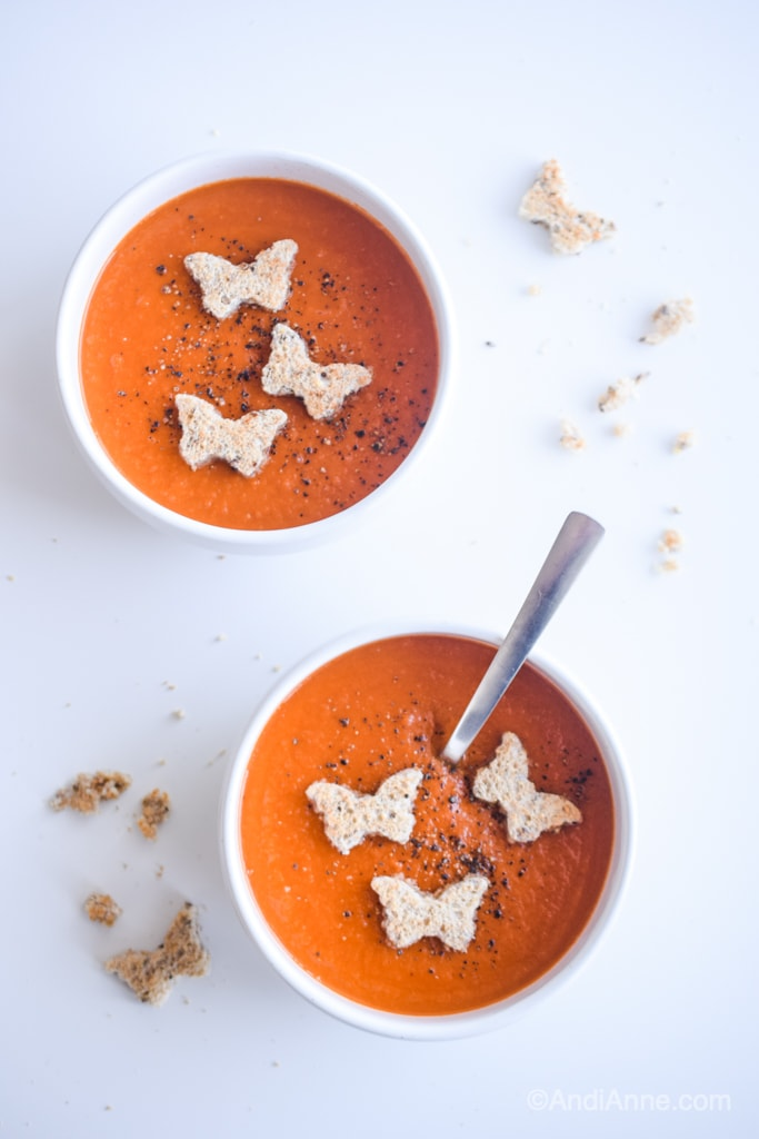 Classic homemade tomato soup with butterfly croutons in white bowls