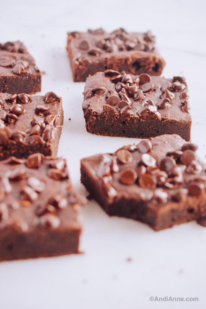 six squares of easy fudgy brownies on counter. One with bite out of corner.