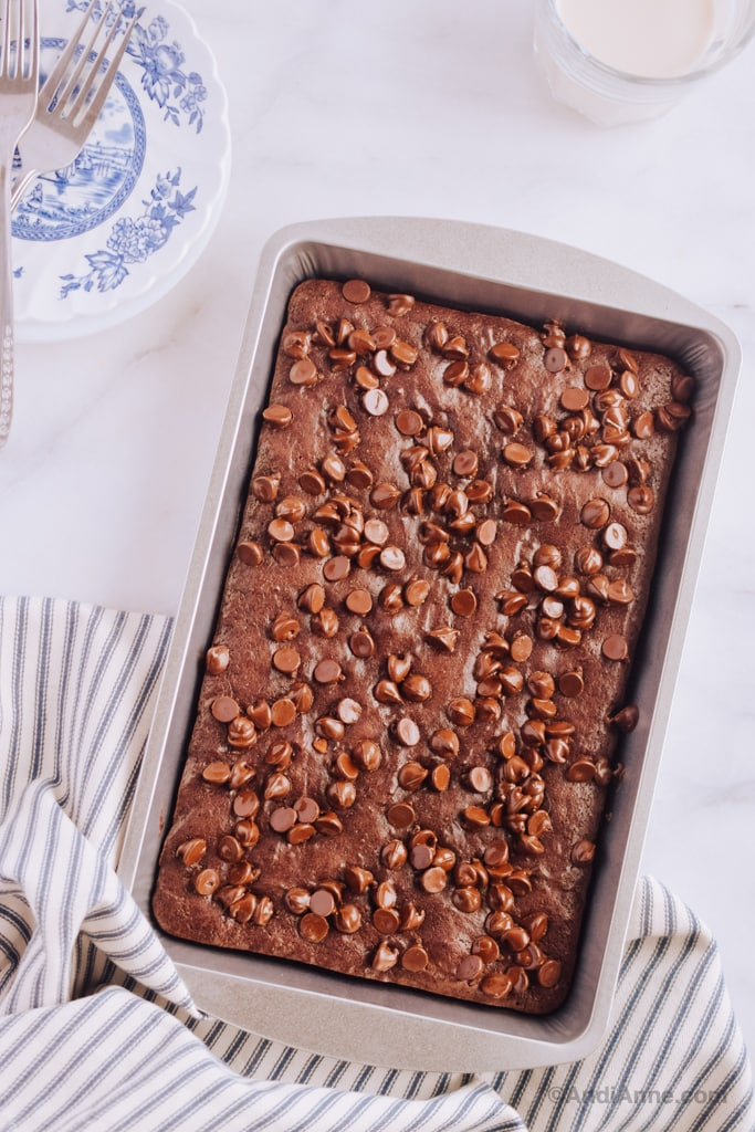 easy fudgy brownies uncut in pan with plates and forks, and a glass of milk beside