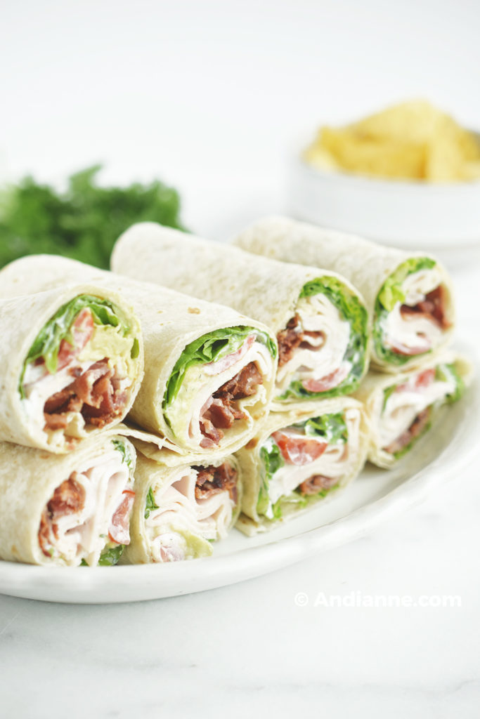 chicken bacon ranch wraps on a plate with parsley and tortilla chips in background