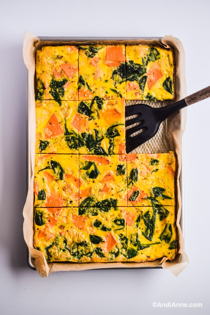 sheet pan eggs with a spatula and parchment paper