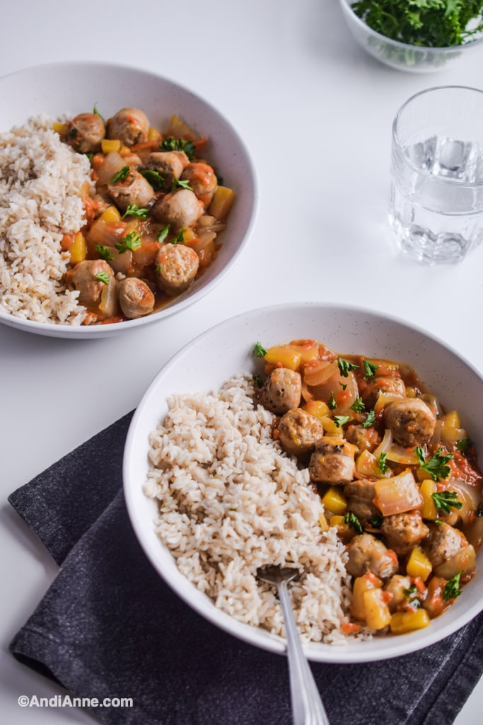sweet and sour sausage with brown rice in two white dishes. Glass of water in background.
