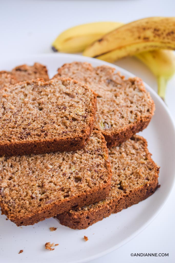 sliced banana bread on white plate with bananas in background