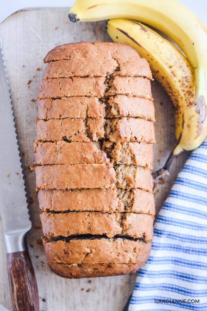 banana bread in thin slices on cutting board with bread knife and ripe bananas