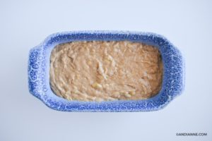banana bread batter poured into blue ceramic loaf pan