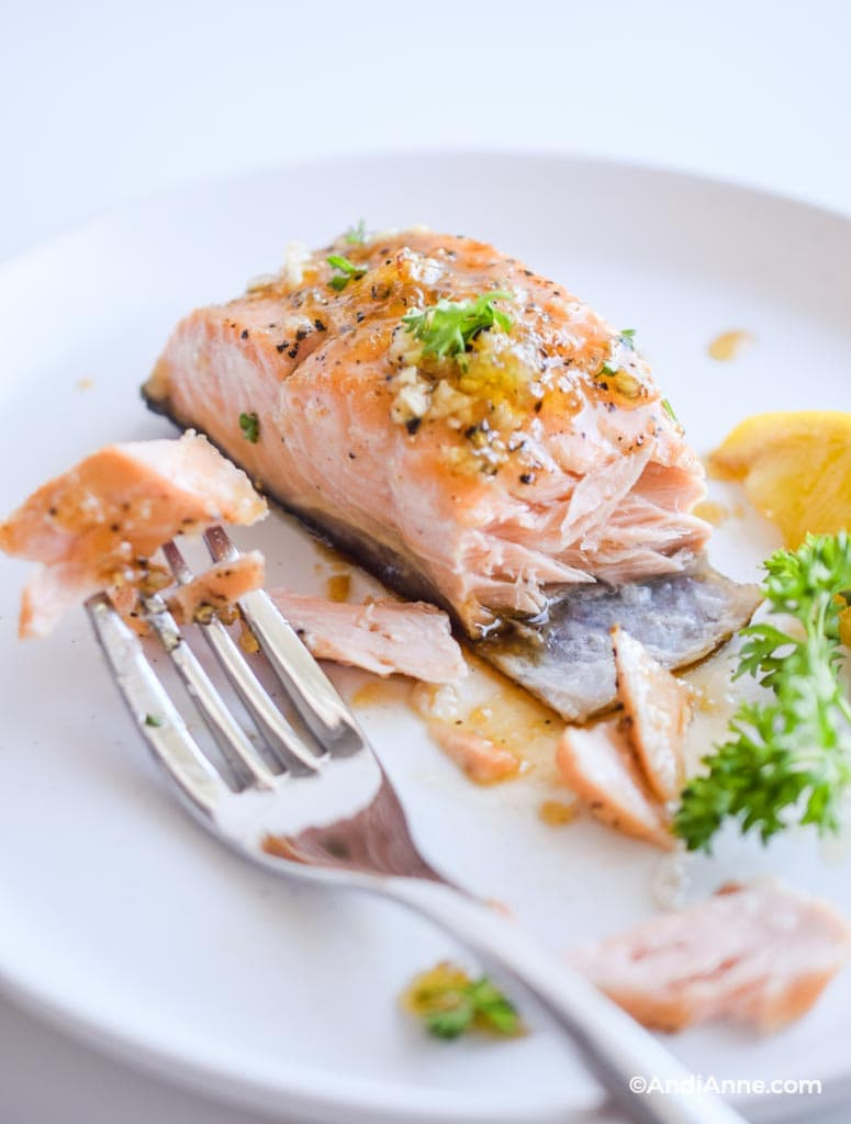 flaked salmon fillet on a white plate with a fork.