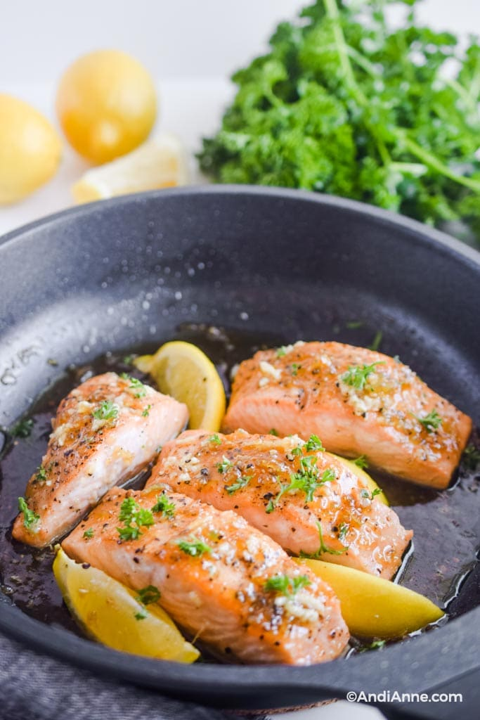 honey garlic salmon fillets in a frying pan with lemons