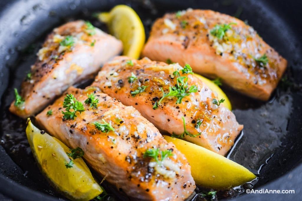 close up detail of honey garlic salmon fillet in a frying pan with lemons