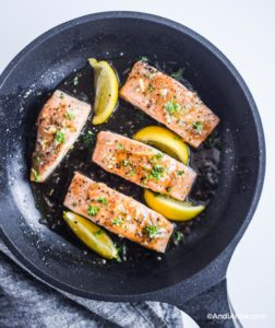 fully cooked honey glazed salmon fillets with lemon slices in frying pan