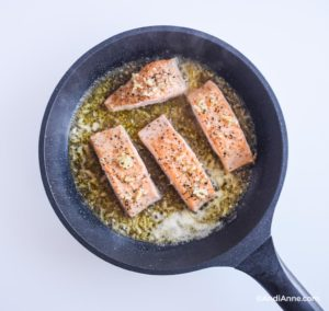 cooking salmon fillets in frying pan with honey glaze sauce surrounding