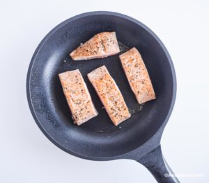 salmon fillets cooking in frying pan, skin side facing down
