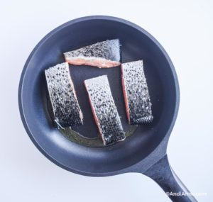 four raw salmon fillets in a frying pan with skin side facing up