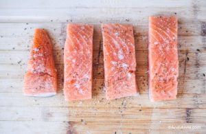 four raw salmon fillets on a cutting board seasoned with salt and pepepr