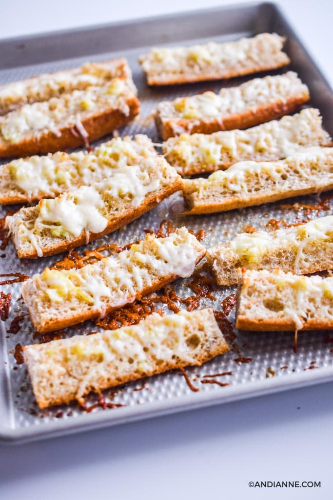 strips of french bread cut up with melted mozzarella cheese on a baking sheet