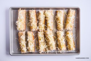sprinkled mozzarella cheese over top of bread slices on baking sheet