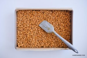 baking sheet with puffed rice mixture pressed inside. Spatula on top
