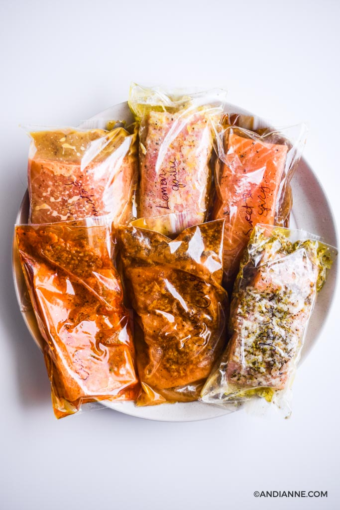 six salmon marinades in plastic bags piled onto a large white plate.