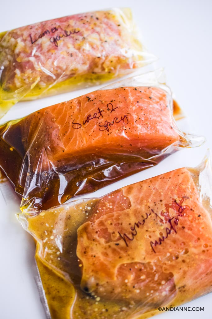 three pieces of salmon marinating inside plastic bags with handwriting on top of each