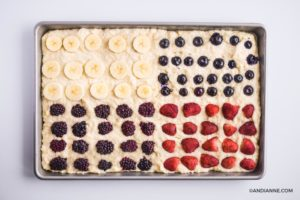 sliced berries and banana pressed into pancake batter in a sheet pan