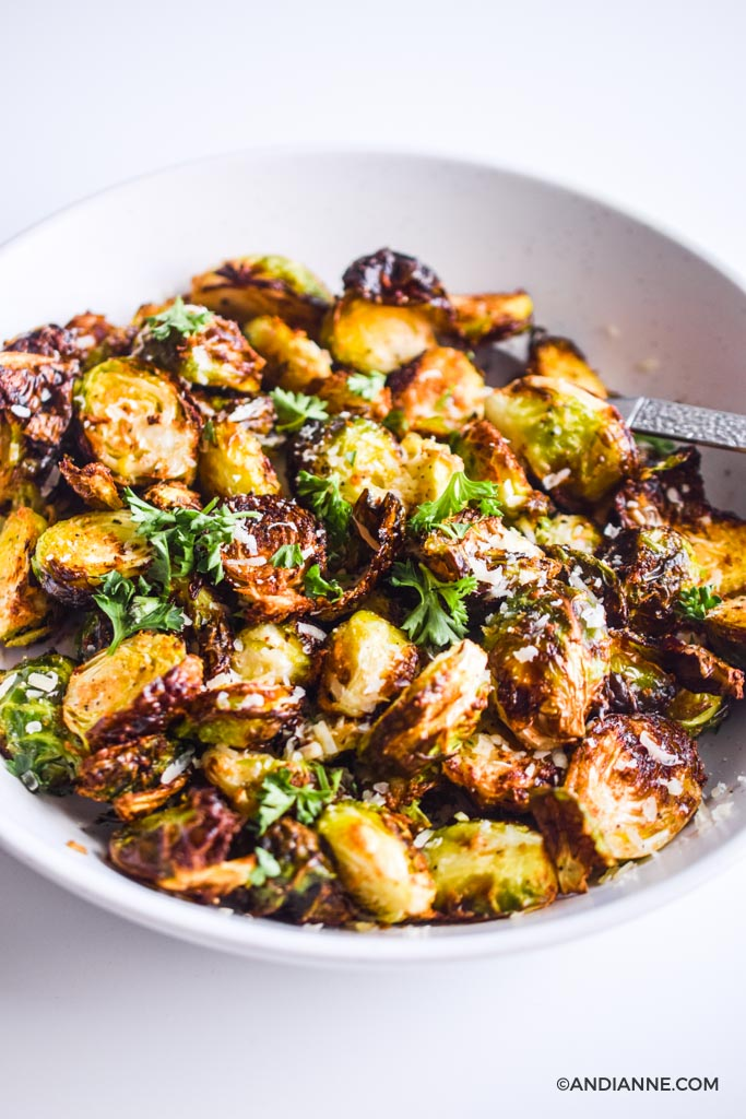 roasted air fryer brussels sprouts with parmesan cheese in white bowl with spoon