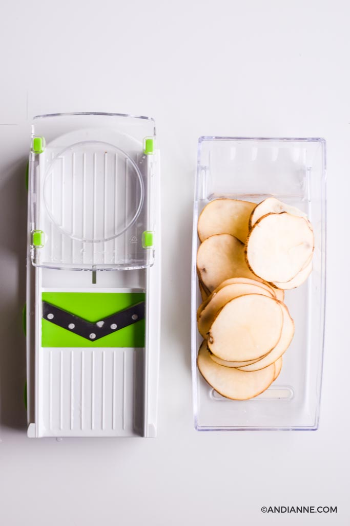 sliced potatoes in a white and green mandolin slicer