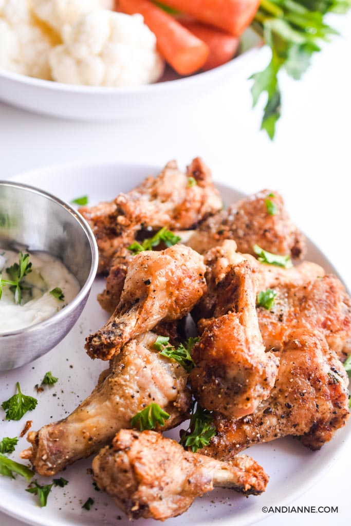 air fryer chicken drumettes on white plate with silver bowl of ranch dip on the left side. Cauliflower, sliced carrots, and sliced celery in a white bowl in the background.