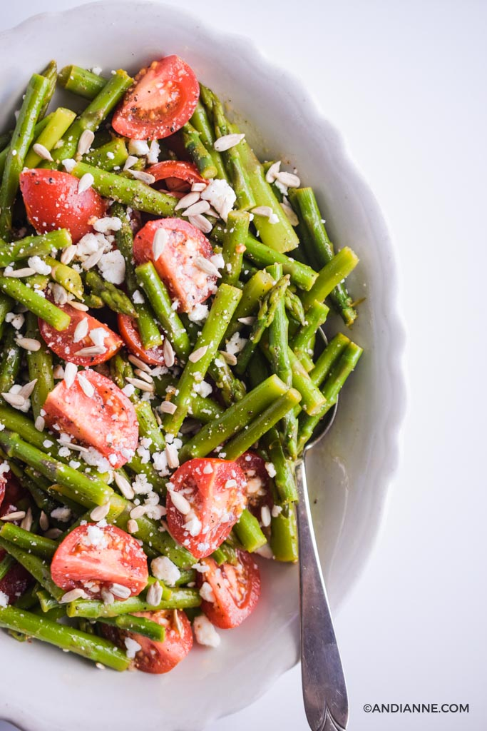 side  of asparagus tomato feta salad in white scalloped edge bowl with spoon