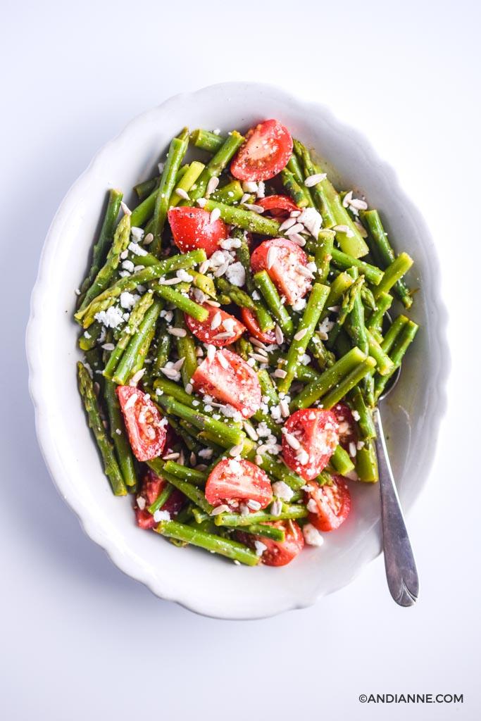 asparagus tomato feta salad in white scalloped edge bowl with spoon