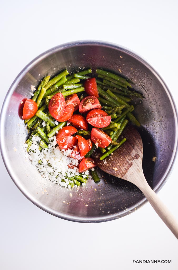 asparagus, tomatoes, feta cheese in a large steel bowl with wooden spoon