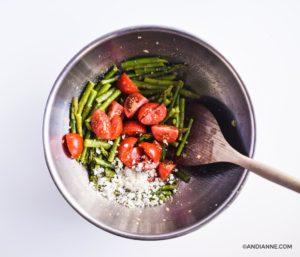 asparagus, tomato, feta in bottom of large steel bowl