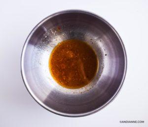 salad dressing in bottom of large metal bowl