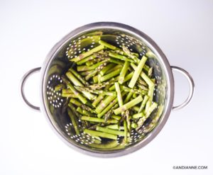 asparagus sliced into thirds in a metal strainer