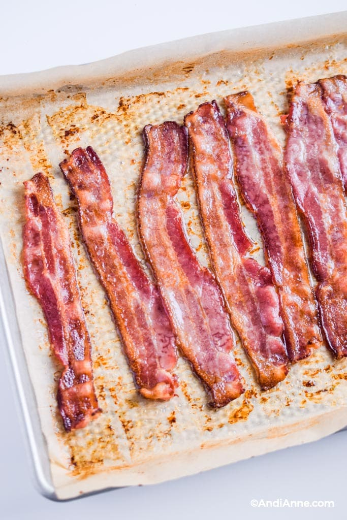cooked bacon in the oven on parchment paper on a baking sheet