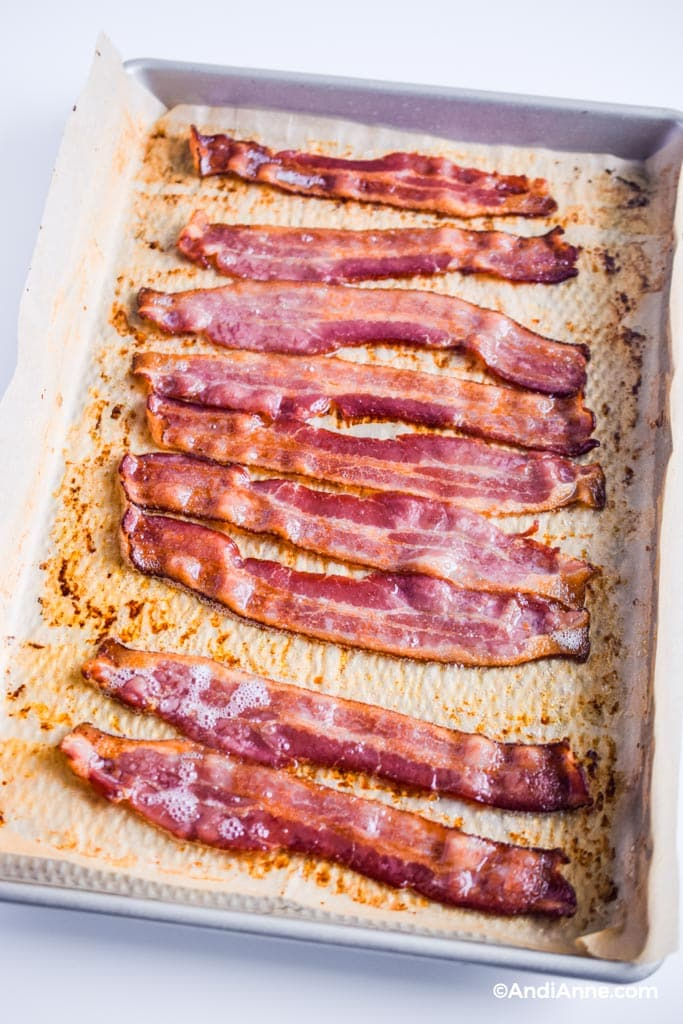 cooked bacon in the oven - bacon on parchment paper on a baking sheet with grease