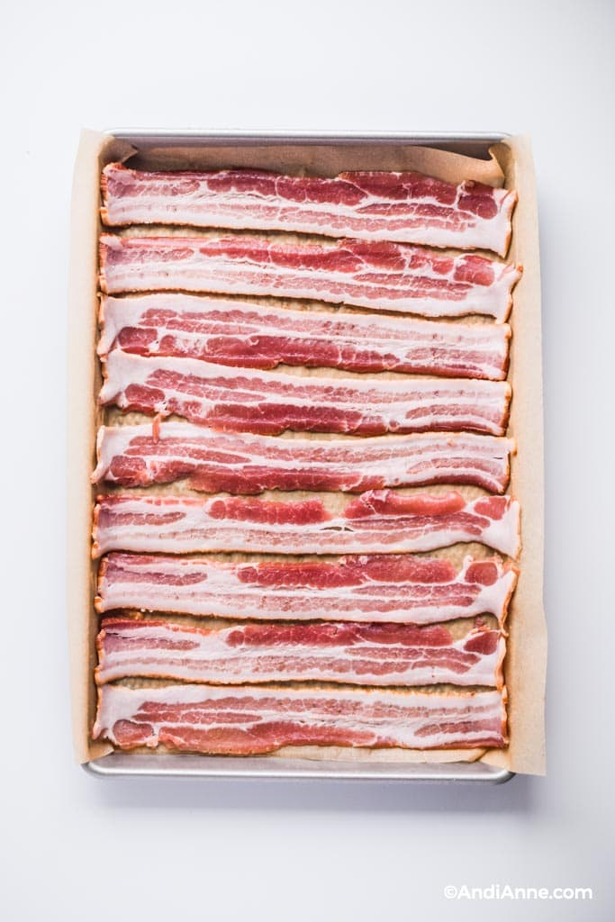 Raw bacon slices on a baking sheet with parchment paper