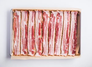 raw bacon in single layer on baking sheet