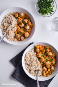 two white plates of rice and sweet and sour sausage recipe with forks. Parsley in small bowl and glass of water to the side.